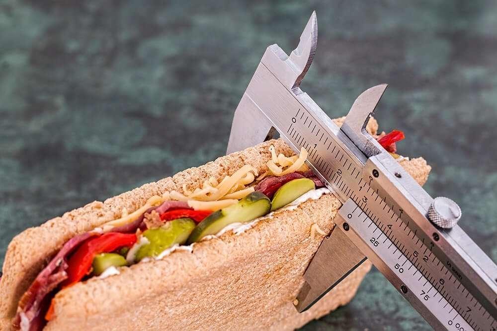 Tape measure measuring size of sandwich